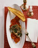 Fried sea bass fillet on tomato slices