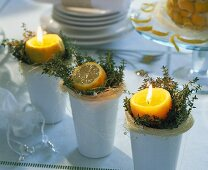 Candles and half a lemon on herbs