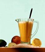 Orange shake in glass jug on crushed ice