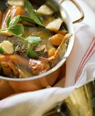 Beef broth with soup vegetables and herbs in copper pan