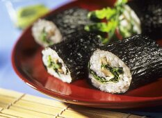 Futo maki with oyster mushrooms and rocket on red plate
