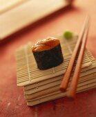 A gunkan maki with sea urchin on bamboo mat with chopsticks