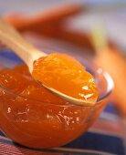 Carrot jelly in bowl and on wooden spoon