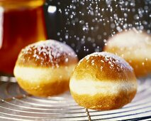 Sprinkling freshly made doughnuts with icing sugar