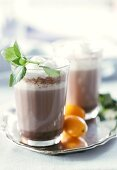 Hot orange and mint cocoa in glasses on tray