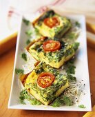 Spinach frittata with cherry tomatoes, cut into pieces