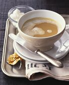 Cup of milky coffee on French newspaper