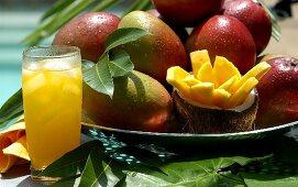 Fresh mangoes, slice of mango and glass of mango juice