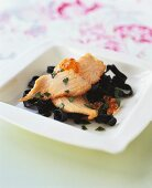 Black ribbon pasta with salmon fillet and caviare