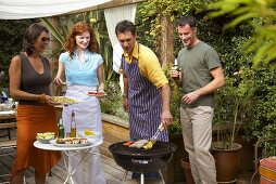 Two couples barbecuing food in garden