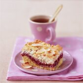 Piece of coconut raspberry cake with tea