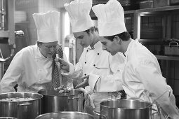 Three chefs checking cooked vegetables
