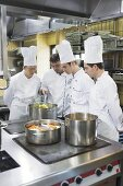 Four chefs checking cooked vegetables