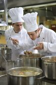 Chefs examining the contents of a pan