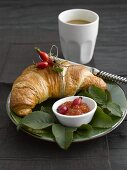 Croissant, rose hip jam and coffee for breakfast