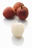 Lychees: three unpeeled and one peeled