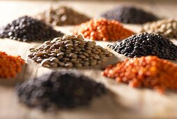 Heaps of different lentils (red, brown, black)