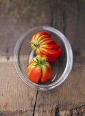 Two tomatoes in glass dish