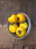 Five yellow beefsteak tomatoes in glass dish