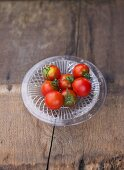 Several tomatoes, variety 'Maigloeckchen', on glass plate