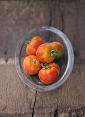 Several peach tomatoes in glass dish
