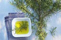 Rosemary branch and small dish of oil