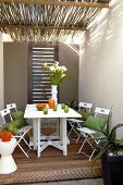 Folding wooden table with chairs on covered terrace