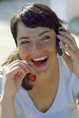 Young woman with a pair of cherries and a mobile phone