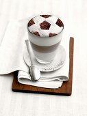 Latte macchiato with milk froth in football design