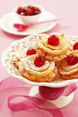 Fried pastries with glacé cherries and icing sugar
