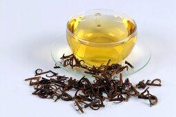 Uncaria-Zweige und Dornen mit Teetasse