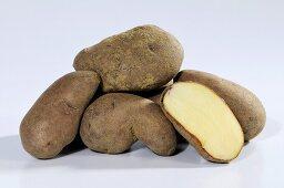 Several potatoes (variety 'Kepplestone Kidney'), whole and halved