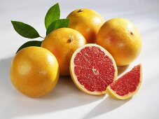 Several pink grapefruits (whole, halved and a wedge)