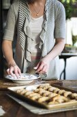 Woman rolling crescent biscuits in icing sugar