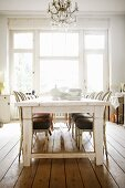 White crockery on white wooden table in front of tall, period windows