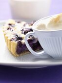 Piece of blueberry tart with cream