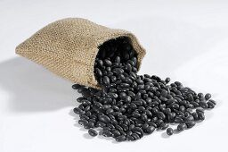Black beans spilling out of hessian sack