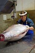 Man cutting tuna with saw at Tsukiji Fish Market in Tokyo