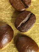 Four coffee beans on gold background (close-up)