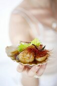 A woman holding grilled scallops