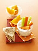 Hummus with vegetable sticks, pita bread and orange wedges for lunch