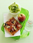 Pizza, apple and salad on lunch box