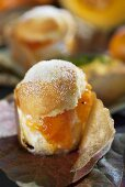 A muffin with Japanese persimmon and pumpkin jam on autumnal leaves