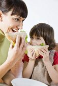 A mother and her little daughter eating sandwiches