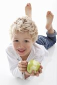 Little boy holding a partly eaten apple
