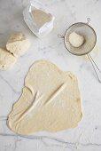 Dough and flour on marble slab
