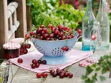 Sour cherries in colander, jars of jam