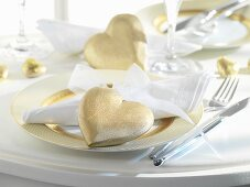 Place-setting for special occasion with gold hearts and gold-rimmed plate