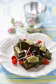 Stuffed vine leaves with tomatoes on cocktail sticks