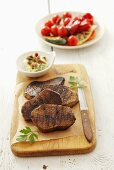 Grilled beefsteaks, garlic butter and tomato salad